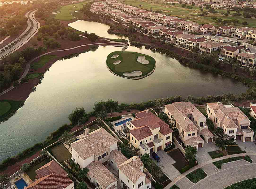 An aerial view of golf course surrounded by a water body at Jumeirah Golf Estates